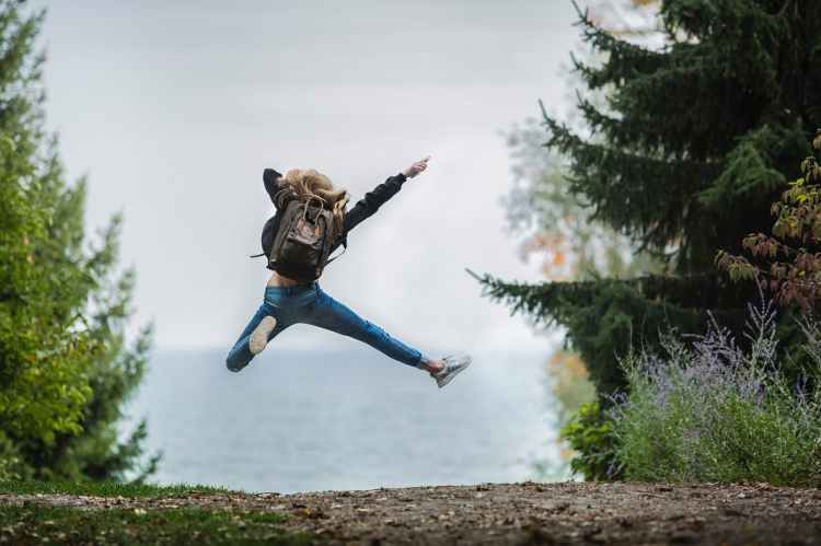 woman jumping for joy with rucksack