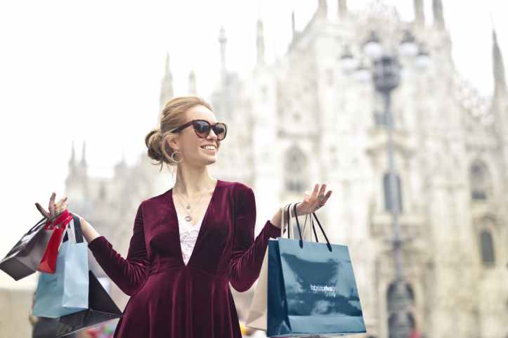 woman wearing maroon velvet plunge neck long sleeved dress while carrying several paper bags photography