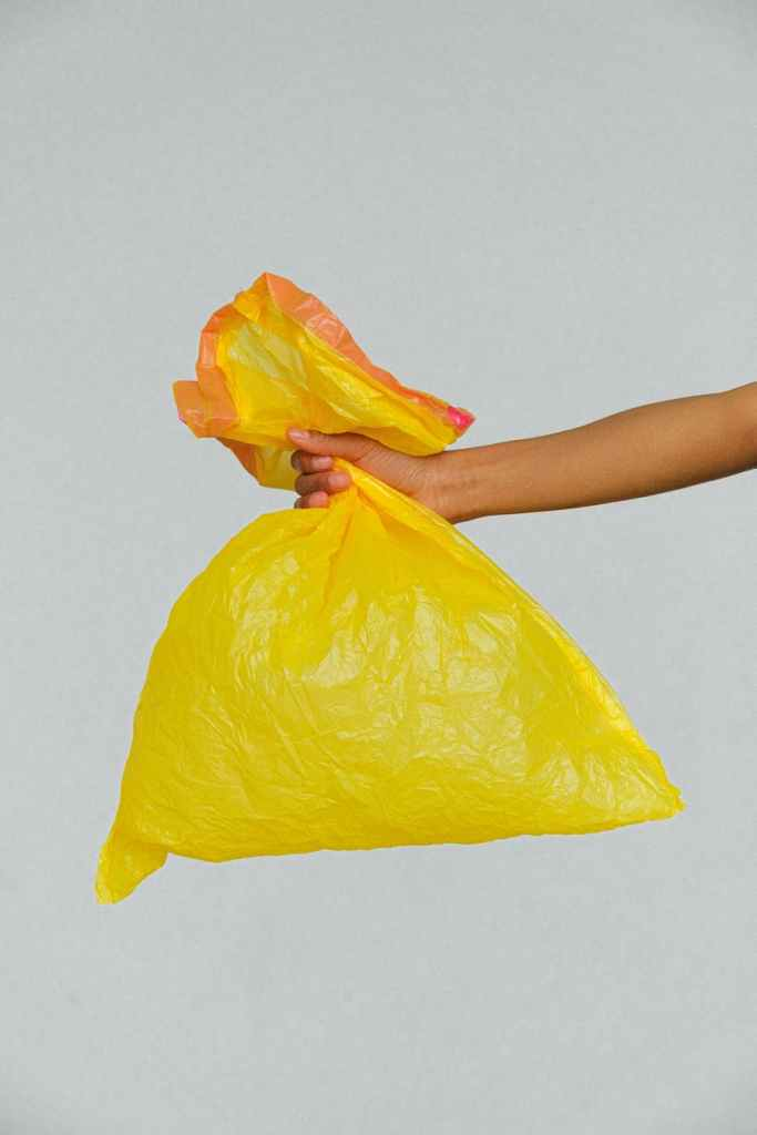 hand holding a yellow plastic bag